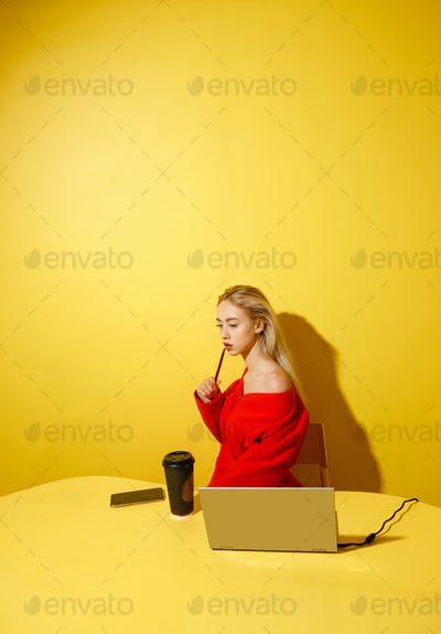 Young fashion girl blogger dressed in stylish red coat sitting at the yellow table with the laptop