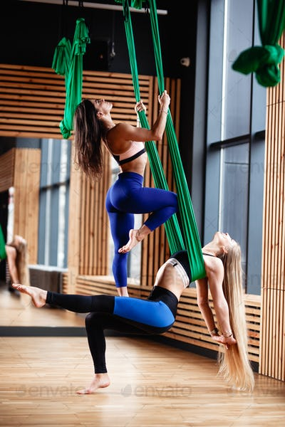 Two young athletic girls brunette and blonde are doing fitness on the green aerial silk in the