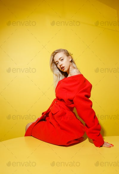 Fashion girl blogger dressed in stylish red coat sitting on the yellow table on the background of