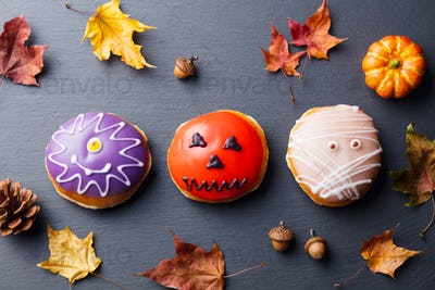 Donuts with Halloween Decoration on Black Slate Background. Top View.