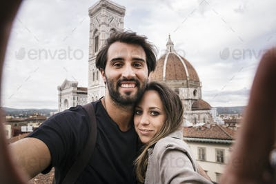 Couple in love visiting Florence Italy and taking a selfie with a smartphone