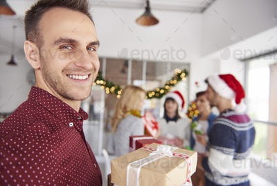 Young man standing in front of camera with Christmas presents