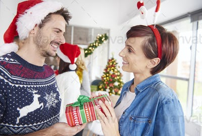 One of couple giving Christmas presents to each other