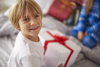 Happy boy opening Christmas presents in the bed