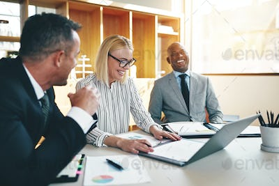 Three laughing businesspeople discussing paperwork together in an office