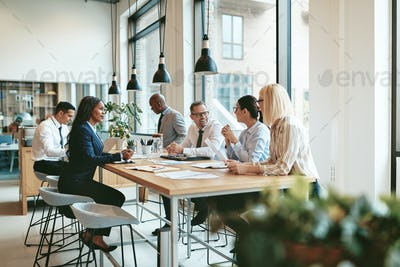 Diverse businesspeople smiling and talking together at an office table