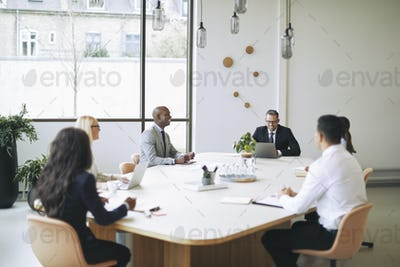 Diverse businesspeople sitting around a boardroom table discussing work