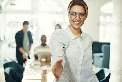 Friendly young businesswoman standing in an office extending a handshake