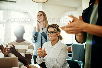 Diverse office colleagues smiling and clapping together during a meeting