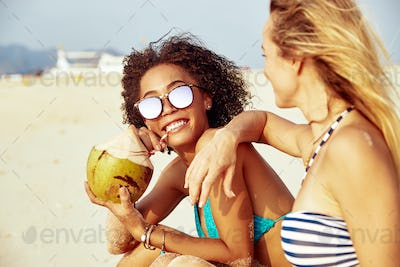 Smiling woman drinking a coconut while suntanning with her friend