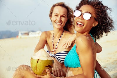 Laughing friends in bikinis suntanning together on a tropical beach