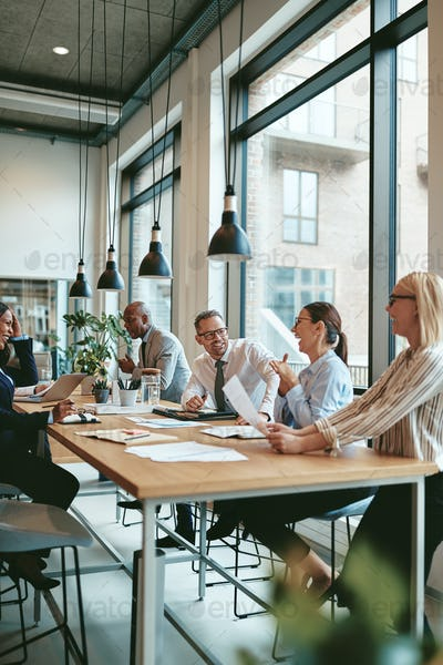 Laughing group of diverse businesspeople talking together around a table