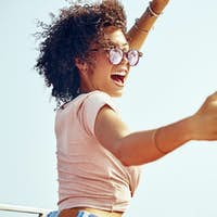 Laughing woman taking selfies on a boat during summer vacation