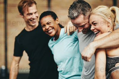 Diverse friends laughing together while standing in a gym