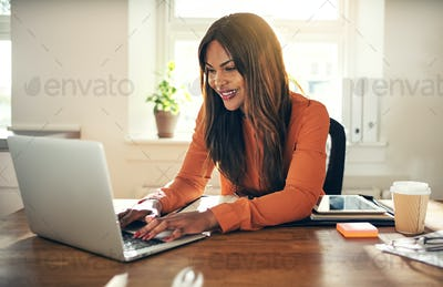 Smiling woman working on a laptop in her home office
