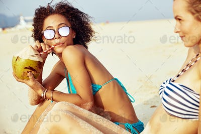 Young woman drinking a coconut while suntanning with a friend