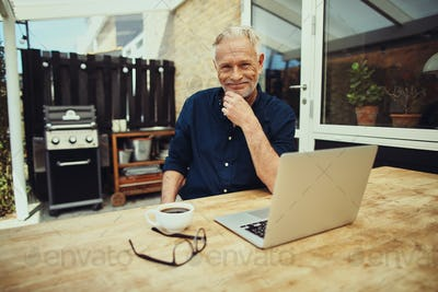 Smiling senior man relaxing on his patio using a laptop