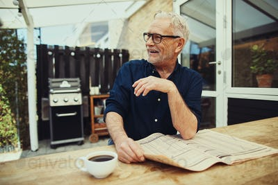 Content senior man sitting at his patio table laughing