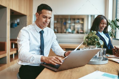 Smiling businessman working on his laptop in a modern office