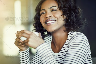 Young African woman laughing while enjoying coffee in a cafe