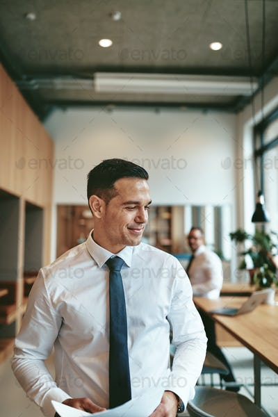 Smiling young businessman walking through a modern office