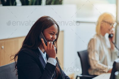 Laughing businesswoman talking on the telephone at an office reception