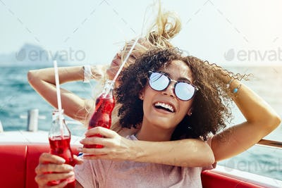 Laughing friends having drinks on a boat during summer vacation