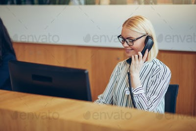 Businesswoman smiling while talking on the telephone in an office