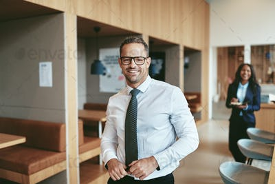 Smiling mature businessman standing in a modern office