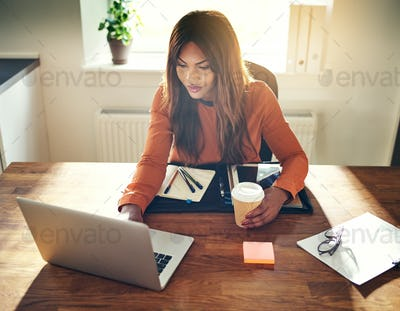 Young woman working and drinking coffee in her home office
