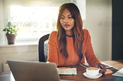 Focused young woman hard at work in her home office