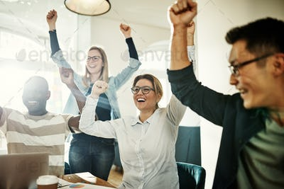 Diverse group of ecstatic colleagues cheering together in an office