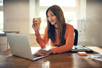 Young entrepreneur drinking coffee and working in her home office