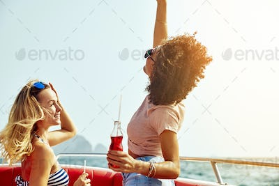 Laughing friends having fun on a boat during summer vacation