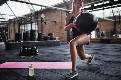 Fit woman working out with a ball at the gym