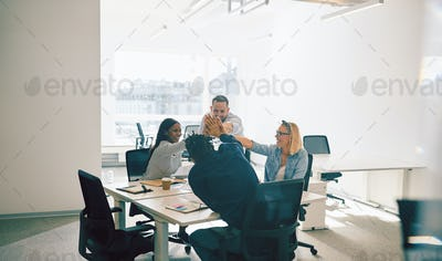 Group of smiling colleagues high fiving during an office meeting