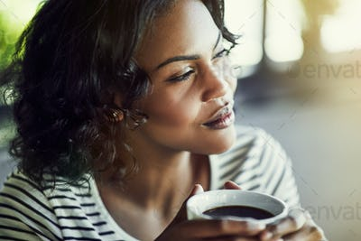 Young African woman drinking a coffee looking deep in thought