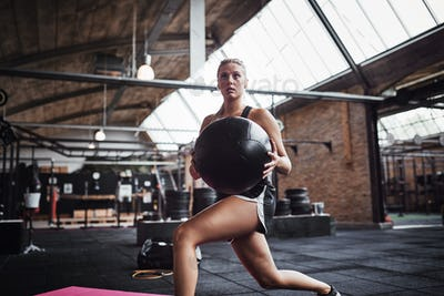 Focused woman working out with a ball in the gym