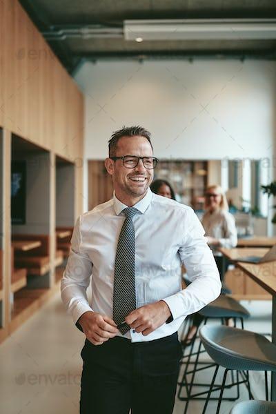 Mature businessman laughing while walking through a modern office