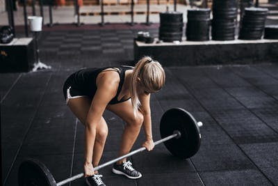 Young woman preparing to lift barbells in a gym