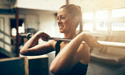 Fit young woman smiling and lifting weights in a gym