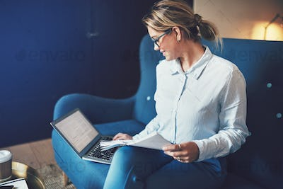 Smiling female entrepreneur reading paperwork and using a laptop