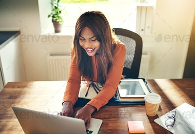 Smiling female entrepreneur working online in her home office