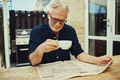 Senior man drinking fresh coffee and reading a newspaper outside