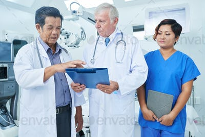 Nurse standing near talking doctors