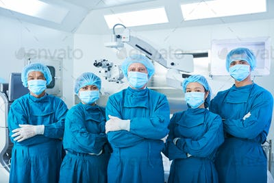 Confident Asian surgeons looking at camera