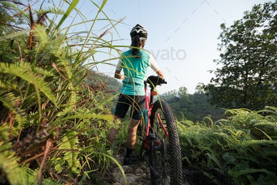 Woman mountain biker looking at the view on sunrise mountain top