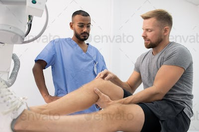 Young sportsman complaining on sick leg or knee while showing it to doctor