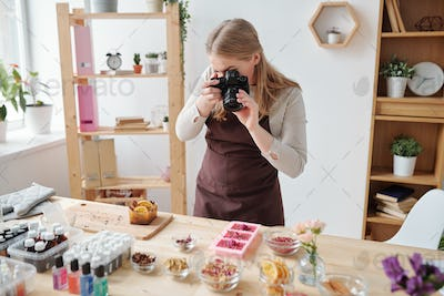 Young woman shooting ingredients and aromatic stuff for making handmade soap