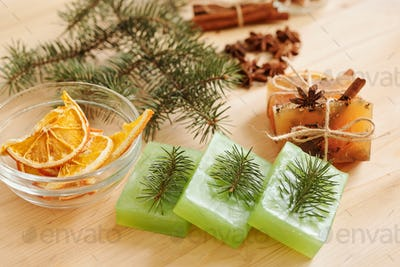 Handmade soap bars with conifer and aromatic spices and orange slices in bowl